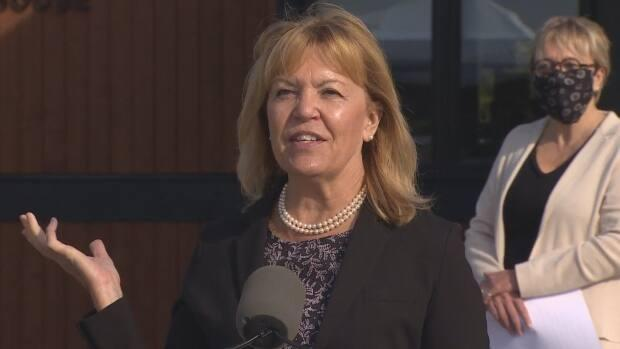 Ontario Health Minister Christine Elliott, left, speaks to reporters outside the Pine River Institute in Mulmur, Ont. at a news conference on Monday. Edyta Pacuk, chair of the facility's board, right, stands behind her. (CBC - image credit)