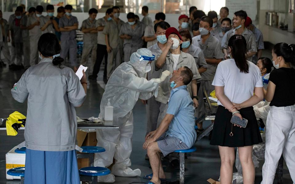 Workers at an auto parts manufacturer get tested for Covid-19 in the factory's canteen in Wuhan in central - Barcroft Media