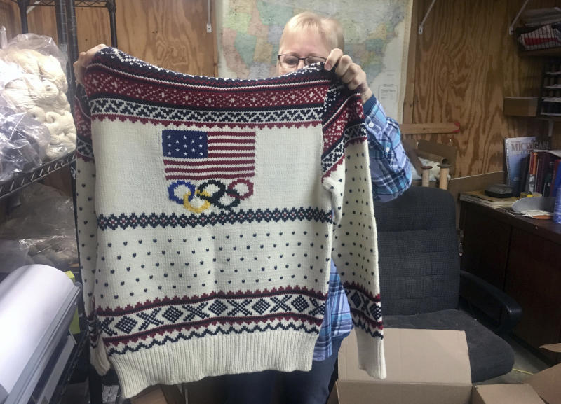 This Oct. 16, 2018 photo shows Debbie McDermott holding up the back side of a Ralph Lauren sweater in East Jordan, Mich., that athletes wore for the 2014 Winter Olympics closing ceremony. The sweater was made using Shepherd's Wool, one of Stonehedge Fiber Mill's yarn lines. (Shireen Korkzan via AP)