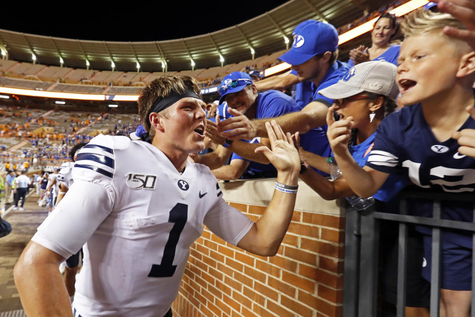 FILE - BYU quarterback Zach Wilson (1) celebrates an overtime win against Tennessee with fans in an NCAA college football game in Knoxville, Tenn., in this Saturday, Sept. 7, 2019, file photo. Trevor Lawrence and Zach Wilson are expected to be the top two picks selected in the NFL Draft on Thursday, April 29, 20212, in Cleveland. (AP Photo/Wade Payne, File)
