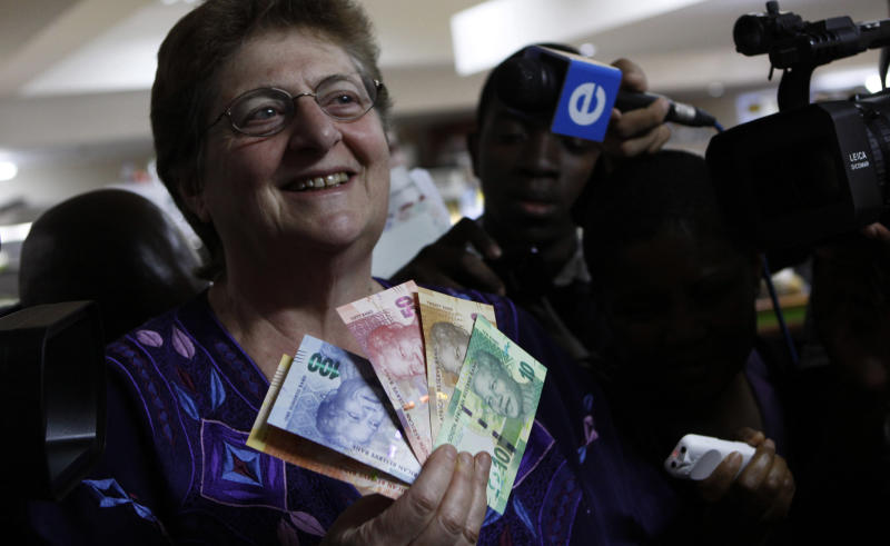 Reserve bank governor Gill Marcus displays bank notes bearing the image of former president Nelson Mandela, in Pretoria, South Africa, Tuesday, Nov. 6, 2012. New South African banknotes featuring the image of former president and anti-apartheid icon Nelson Mandela are going into circulation. Reserve bank governor Gill Marcus made the first purchase using the new rand notes at a small shop in Pretoria Tuesday. She says the country tries to upgrade its notes every seven years for security reasons as technologies change. (AP Photo/Denis Farrell)