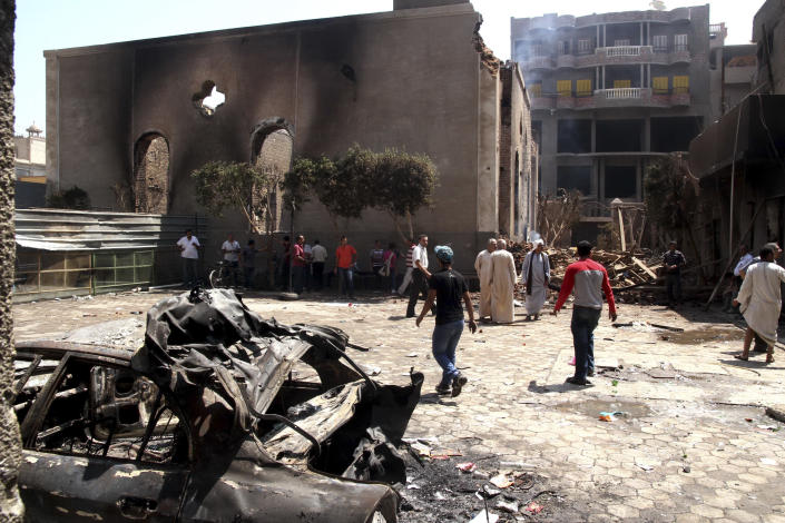 Egyptian gather in the ruins of the Evangelical Church of Malawi after it was ransacked, looted and burned on Thursday by an angry mob, in Malawi, south of Minya, Egypt, Saturday, Aug. 17, 2013. In the province of Minya south of Cairo, protesters attacked two Christian churches, security officials said. Many of Morsi's supporters have criticized Egypt's Christian minority for largely supporting the military's decision to remove him from office, and dozens of churches have been attacked this week. (AP Photo/Roger Anis, El Shorouk Newspaper) EGYPT OUT