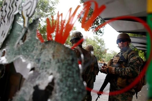 Chilean army soldiers protect a mall ransacked by protesters in Santiago, Chile (AFP Photo/Pablo VERA)