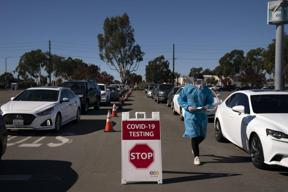 FILE - In this Nov. 16, 2020, file photo, student nurse Ryan Eachus collects forms as cars line up for COVID-19 testing at a testing site set up the OC Fairgrounds in Costa Mesa, Calif. Congress is bracing for President-elect Joe Biden to move beyond the Trump administration's state-by-state approach to the COVID-19 crisis and build out a national strategy to fight the pandemic and distribute the eventual vaccine. (AP Photo/Jae C. Hong, File)