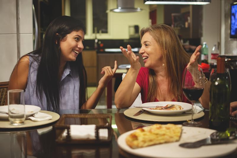 Mother and daughter eating pizza at dining table