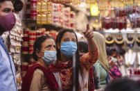 Indians wearing masks as a precaution against the coronavirus shop for bangles ahead of Hindu festivals in Jammu, India, Sunday, Oct.25, 2020. Weeks after India fully opened up from a harsh lockdown and began to modestly turn a corner by cutting new coronavirus infections by near half, a Hindu festival season is raising fears that a fresh surge could spoil the hard-won gains. (AP Photo/Channi Anand)