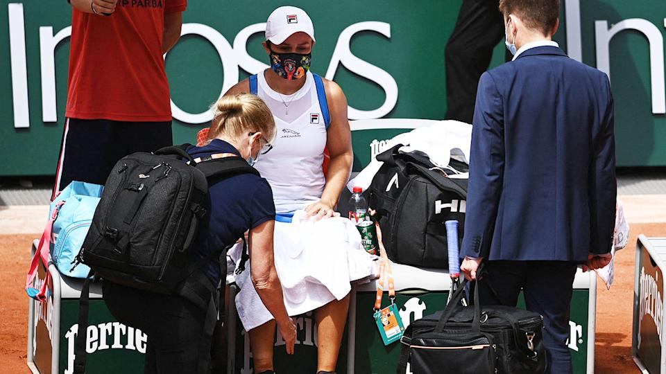 Ash Barty, pictured here being treated by medical staff during her match against Magda Linette.