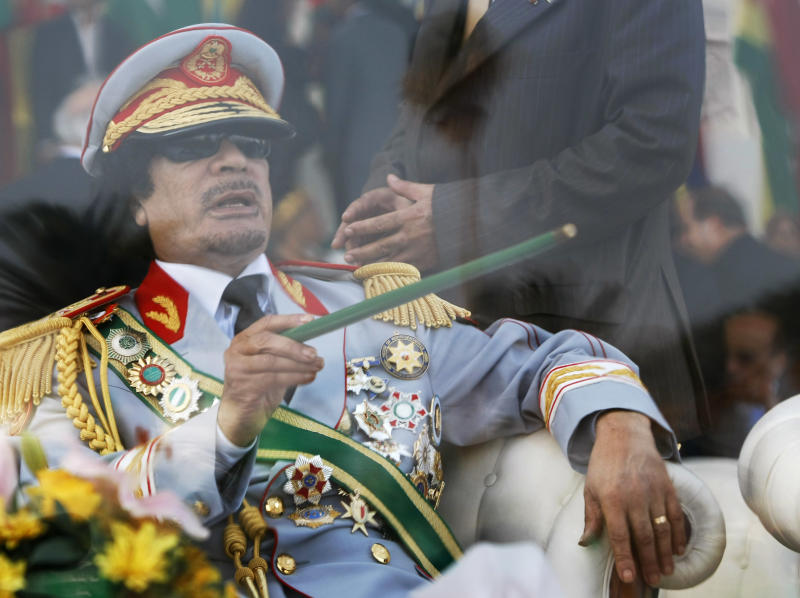 FILE - In this Tuesday, Sept. 1, 2009 file photo, Libyan leader Moammar Gadhafi gestures with a green cane as he takes his seat behind bulletproof glass for a military parade in Green Square, Tripoli, Libya. Libyan special forces stormed a two-day-old protest encampment in the country's second largest city of Benghazi, clearing the area early Saturday, Feb. 19, 2011, said witnesses, as a human rights group estimate scores of people have died in the harsh crackdown on days of demonstrations.