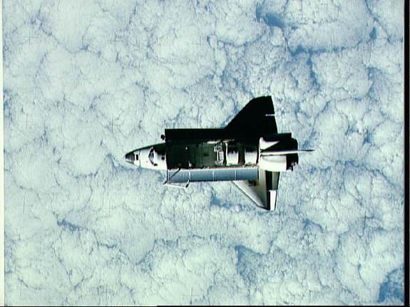 This full view of Challenger in space was taken by a satellite. A heavily cloud-covered portion of the Earth forms the backdrop for this scene of Challenger in orbit. This image was taken during Challenger's STS-7 mission, which launched on Jun
