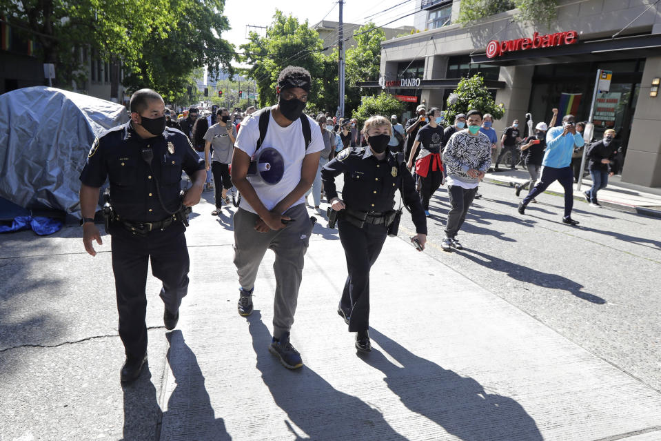 """A protester who did not give his name walks with Seattle Police assistant chiefs Adrian Diaz, left, and Deanna Nollette, right, Thursday, June 11, 2020, inside what is being called the """"Capitol Hill Autonomous Zone"""" in Seattle. The officers were attempting to walk to the department's East Precinct building, which has been boarded up and abandoned except for a few officers inside, but the protester, in a move that angered some other protesters, said he would walk with the officers to a side entrance of the precinct rather than have them walk directly through a crowd of angry protesters.(AP Photo/Ted S. Warren)"""