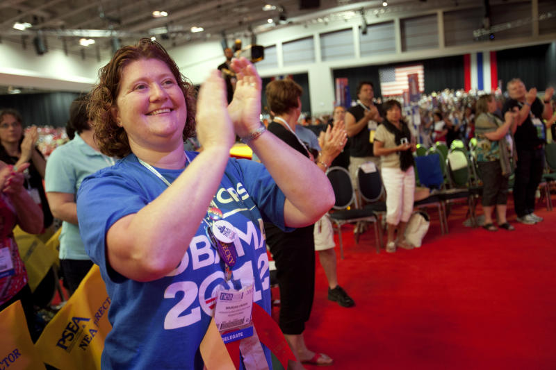 """Wearing a shirt that says """"Educators for Obama 2012,"""" Marsha Fabian, a teacher, of Lancaster, Penn., claps during the National Education Association's annual convention in Washington, on Thursday, July 5, 2012. (AP Photo/Jacquelyn Martin)"""