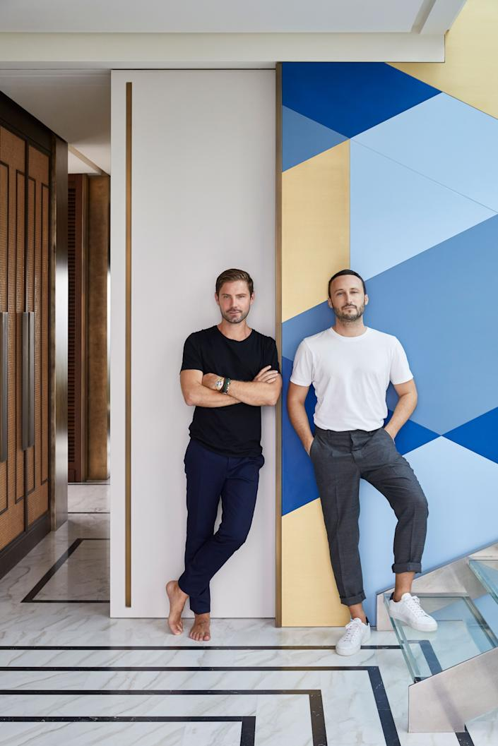 "<div class=""caption""> Emil Humbert (left) and Christophe Poyet standing in front of the wall composed of wood panels in brass and three shades of blue—Marine, Azur, and French. The floor is Calacatta Sponda and Nero Marquina; the cupboards in the background are caning, stained oak, and bronze handles. </div>"