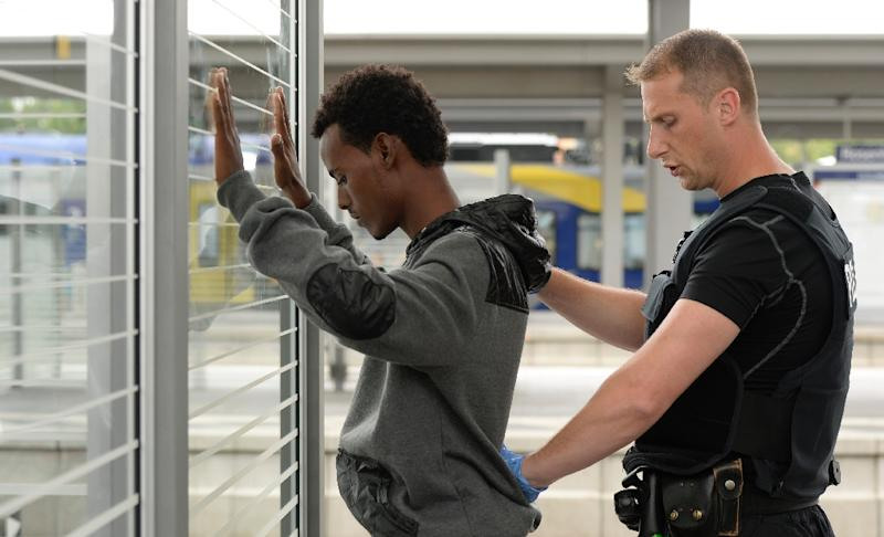 An officer of the German Federal Police pats down a refugee at a registration point at the railway station in Rosenheim, southern Germany, on July 29, 2015 (AFP Photo/Christof Stache)