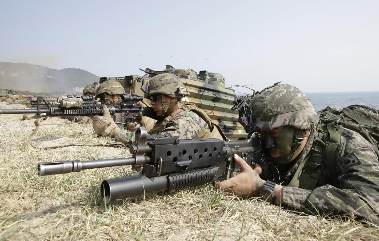 In this 2015 photo, a South Korean Marine, right, and U.S. Marines aim their weapons near amphibious assault vehicles during the U.S.-South Korea joint landing military exercises. (Photo: Lee Jin-man/AP)