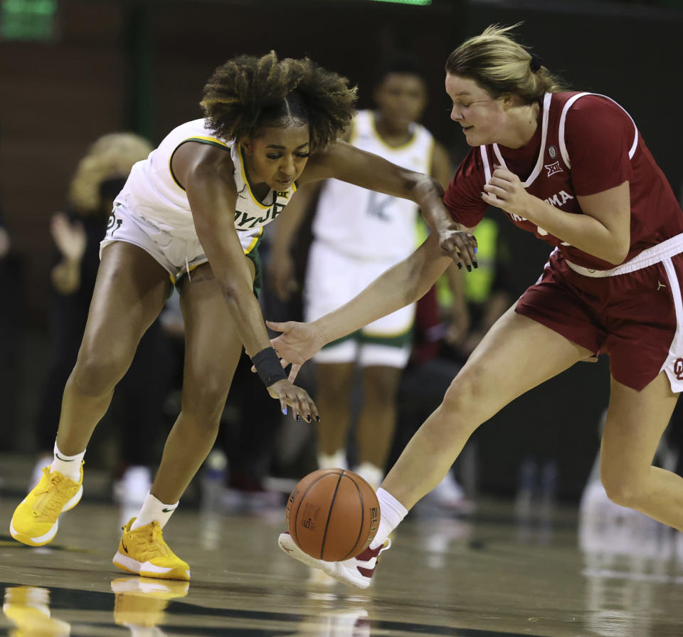 Baylor guard DiDi Richards, left, reaches for the ball over Oklahoma forward Mandy Simpson, right, in the first half of an NCAA college basketball game, Saturday, Jan. 23, 2021, in Waco, Texas. (Rod Aydelotte/Waco Tribune-Herald via AP)