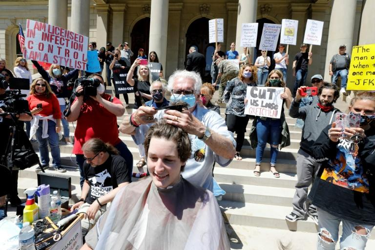 Barber Karl Manke, who lost his license for violating lockdown rules by opening his business, gave haircuts at a protest outside Michigan's state capitol building (AFP Photo/JEFF KOWALSKY)
