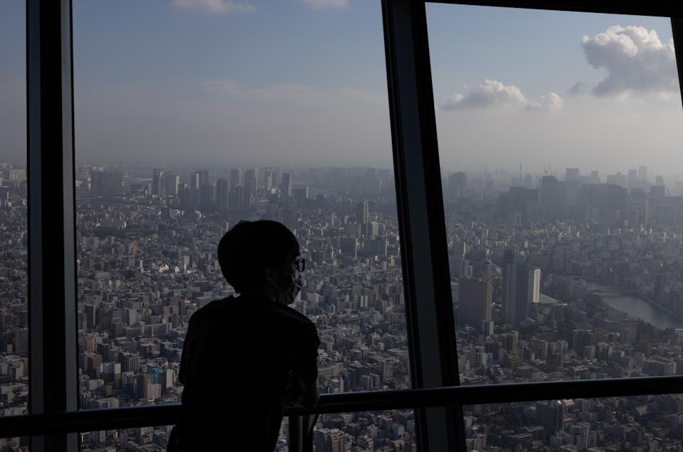 A visitor wearing a face mask views the Tokyo skyline on July 28.