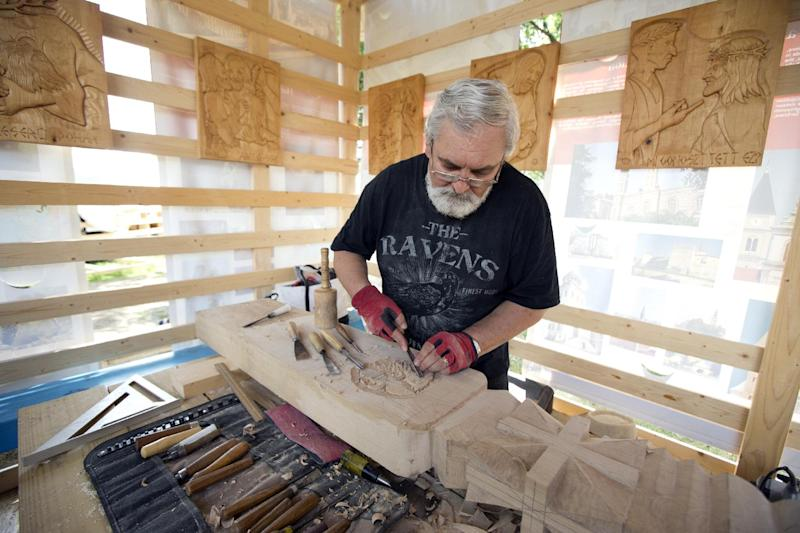 "In this July 3, 2013 photo, sculptor and carver Jakab Gyorgy, of Pomaz, Hungary, works on a wooden carving at the 47th annual Smithsonian Folklife Festival on the National Mall in Washington. Hungarian structures are part of the ""Hungarian Roots to Revival"" program in this year's Smithsonian Folklife Festival _ and a personal thrill for the team of carpenters from Hungary who arrived a month prior to the festival to construct the 23-foot Peacock Tower, the Dance Barn and other buildings. (AP Photo/Manuel Balce Ceneta)"