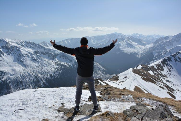 Man standing at the top of a mountain