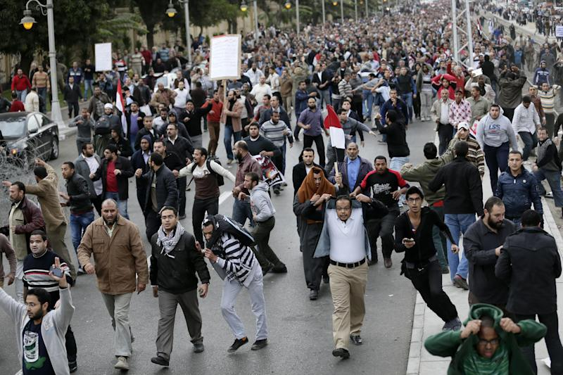 Egyptian President Mohammed Morsi's supporters clash with opponents, not pictured, outside the presidential palace, in Cairo, Egypt, Wednesday, Dec. 5, 2012. Wednesday's clashes began when thousands of Islamist supporters of Morsi descended on the area around the palace where some 300 of his opponents were staging a sit-in. (AP Photo/Hassan Ammar)