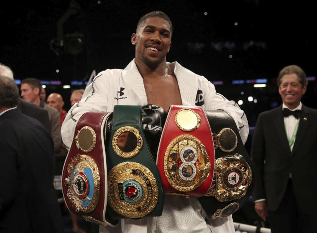 "Anthony Joshua celebrates with his belts after victory over <a class=""link rapid-noclick-resp"" href=""/ncaaf/players/252304/"" data-ylk=""slk:Joseph Parker"">Joseph Parker</a> to become the WBA, IBF and WBO heavyweight champion at the Principality Stadium in Cardiff, Wales, Saturday March 31, 2018. (AP)"
