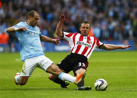 Manchester City's Pablo Zabaleta (L) challenges Sunderland's Lee Cattermole during their English League Cup final soccer match at Wembley Stadium in London March 2, 2014. REUTERS/Eddie Keogh