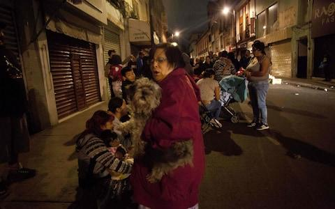 People gather on a street in downtown Mexico City during an earthquake - Credit: AFP