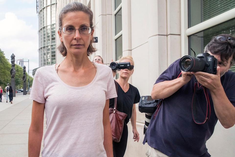 Clare Bronfman, left, leaves federal court, Tuesday, July 24, 2018, in Brooklyn. Bronfman, an heiress to the Seagram's liquor fortune and three other people were arrested on Tuesday in connection with the investigation of a self-improvement organization accused of branding some of its female followers and forcing them into unwanted sex.