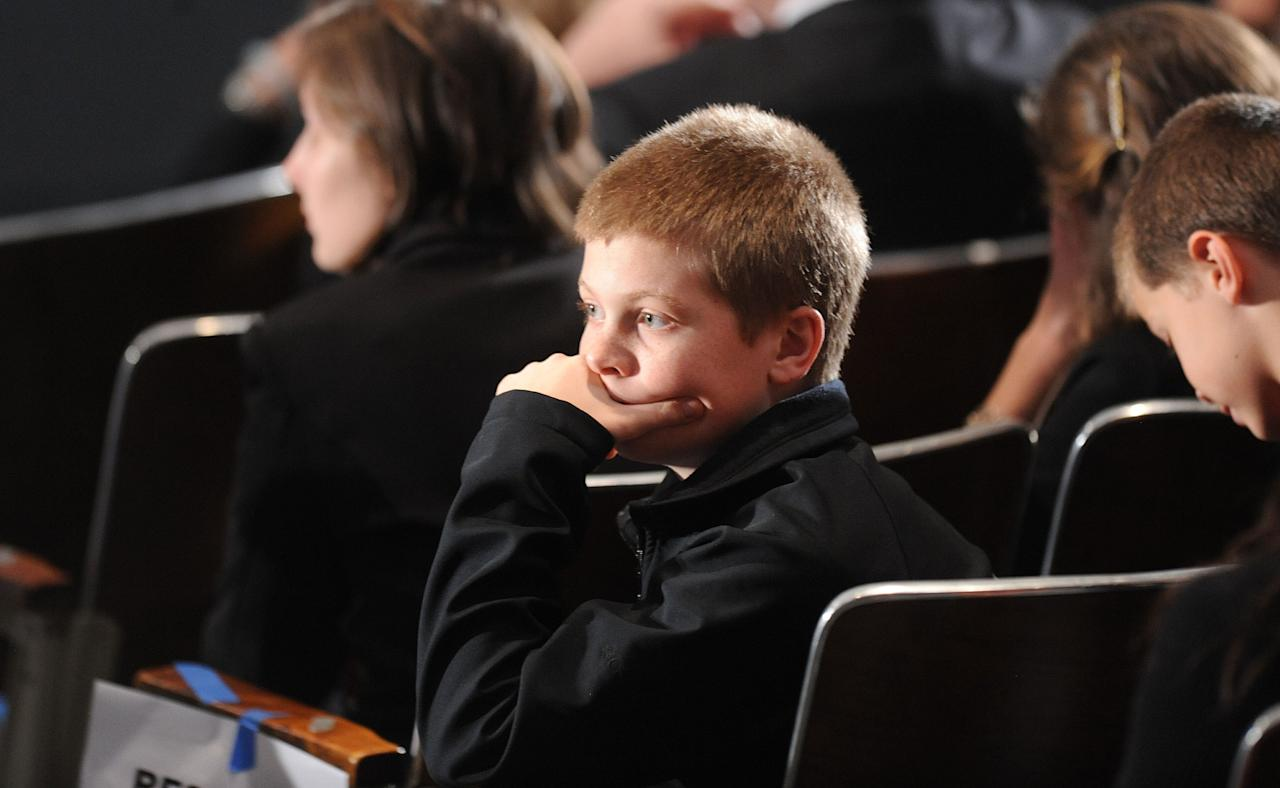 NEWTOWN, CT - DECEMBER 16:  A young boy waits for U.S. President Barack Obama to speak at an interfaith vigil for the shooting victims from Sandy Hook Elementary School on December 16, 2012 at Newtown High School in Newtown, Connecticut. Twenty-six people were shot dead, including twenty children, after a gunman identified as Adam Lanza opened fire at Sandy Hook Elementary School. Lanza also reportedly had committed suicide at the scene. A 28th person, believed to be Nancy Lanza, found dead in a house in town, was also believed to have been shot by Adam Lanza. (Photo by Olivier Douliery-Pool/Getty Images)