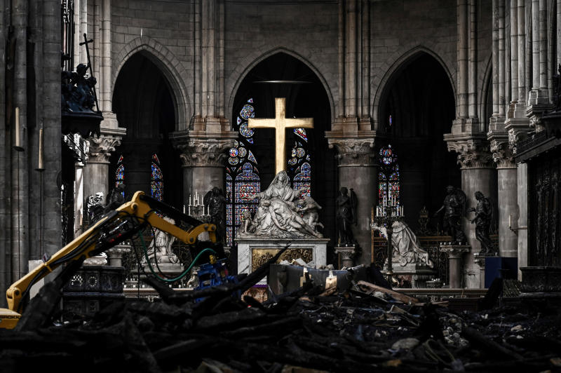 Rubble lies below the Pieta sculpture and a cross inside the Notre Dame de Paris cathedral as Canadian Prime Minister Justin Trudeau visits on Wednesday May 15, 2019 in Paris. (Philippe Lopez/Pool via AP)