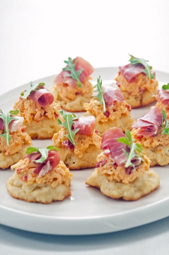 """<p>Rich and savory, these bites will change how you feel about game-day foods. Enjoy a cheese-filled mouthful with every bite you take, along with a nice hint of baby arugla and a buttery biscuit. Yes, please.</p> <p><strong>Get the recipe</strong>: <a href=""""https://www.popsugar.com/food/Pimento-Cheese-Prosciutto-Appetizer-29053551"""" class=""""link rapid-noclick-resp"""" rel=""""nofollow noopener"""" target=""""_blank"""" data-ylk=""""slk:pimento cheese and prosciutto biscuits"""">pimento cheese and prosciutto biscuits</a> </p>"""