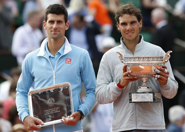Spain's Rafael Nadal, right, holds the trophy after winning the final of the French Open tennis tournament against Serbia's Novak Djokovic, left, at the Roland Garros stadium, in Paris, France, Sunday, June 8, 2014. Nadal won in four sets 3-6, 7-5, 6-2, 6-4
