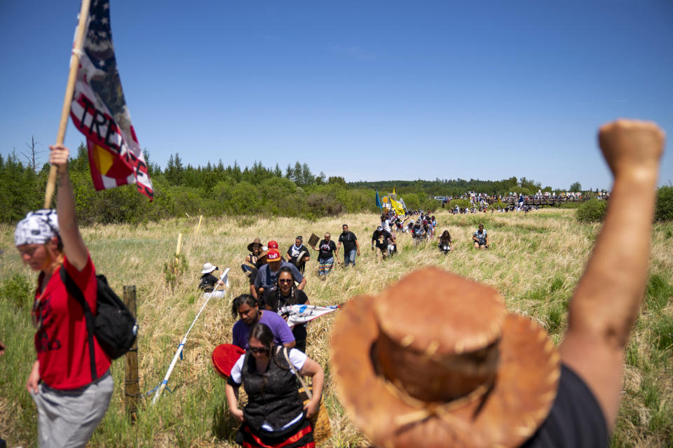 """Indigenous leaders and """"water protectors"""" march through swamp land to the boardwalk leading to an Enbridge pipeline construction site, on Monday, June 7, 2021, in Clearwater County, Minn. More than 2,000 Indigenous leaders and """"water protectors"""" gathered in Clearwater County from around the country to protest the construction of Enbridge Line 3. The day started with a prayer circle and moved on to a march to the Mississippi headwaters where the oil pipeline is proposed to be built. (Alex Kormann/Star Tribune via AP)"""