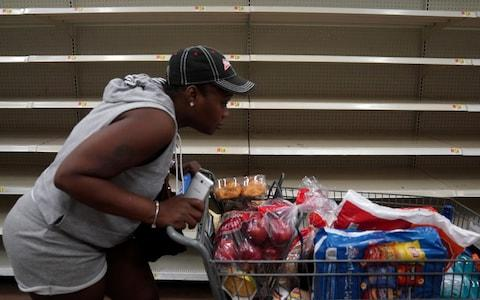 A woman with a full cart walks past empty shelves where bread is normally sold in a Walmart store in advance of Hurricane Irma's expected arrival in North Miami Beach - Credit: CARLO ALLEGRI/Reuters