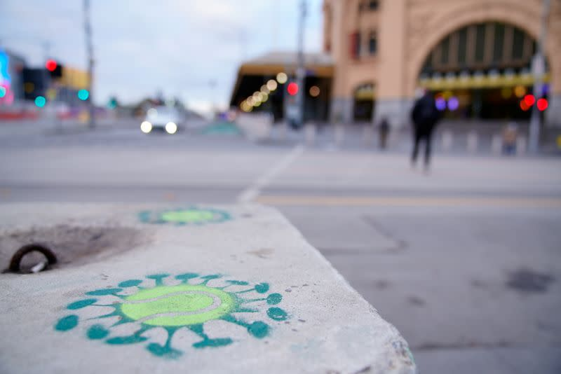 Coronavirus graffiti is seen on the first day of a seven-day COVID-19 lockdown in Melbourne