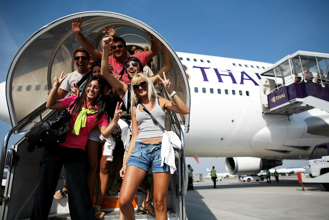 BANGKOK, THAILAND -DECEMBER 03: Passengers exit Thai Airways flight from Phuket, the first to arrive after the end of the seige, lands at Suvarnabhumi International Airport on December 3, 2008 in Bangkok, Thailand. Yesterday, a court dissolved Thailand's top three ruling parties for electoral fraud, banned the prime minister from politics for five years and thus brought down a government that has faced months of protests. Deputy Prime Minister Chaowarat Chanveerakul will become the caretaker prime minister. The on-going political crisis during the holiday season stranded 300,000 foreign tourists, paralysing Thailand's lucrative tourist industry.  (Photo by Chumsak Kanoknan/Getty Images)