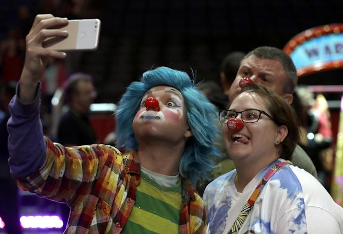 """A Ringling Bros. and Barnum & Bailey clown takes a selfie with Jennifer and Kevin Fox, of Fort Pierce, Fla., during a pre show for fans Saturday, Jan. 14, 2017, in Orlando, Fla. The Ringling Bros. and Barnum & Bailey Circus will end the """"The Greatest Show on Earth"""" in May, following a 146-year run of performances. Kenneth Feld, the chairman and CEO of Feld Entertainment, which owns the circus, told The Associated Press, declining attendance combined with high operating costs are among the reasons for closing. (AP Photo/Chris O'Meara)"""