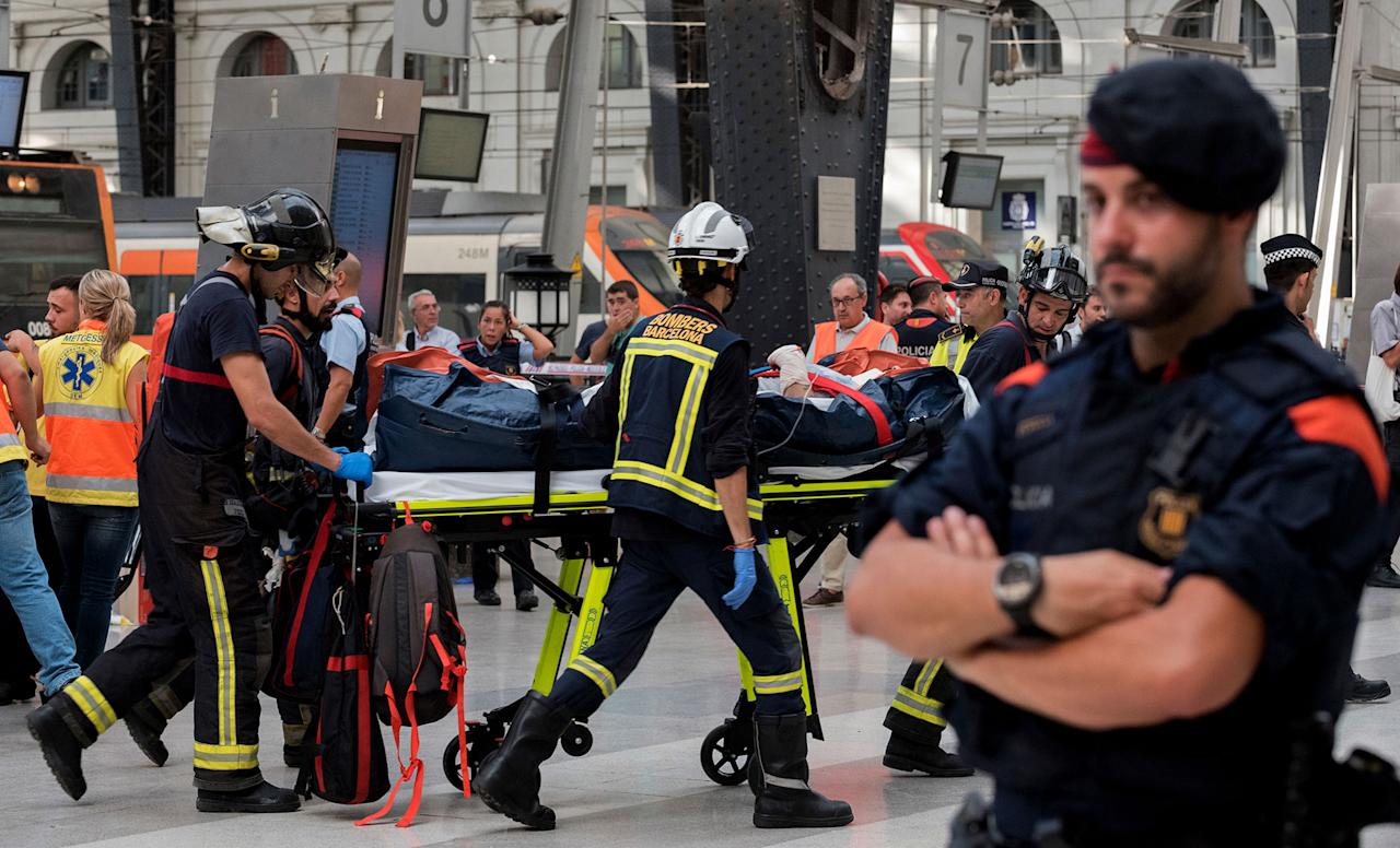<p>An injured passenger is taken away on a stretcher from a train station in Barcelona, Spain, Friday July 28, 2017. (Photo: Adrian Quiroga/AP) </p>