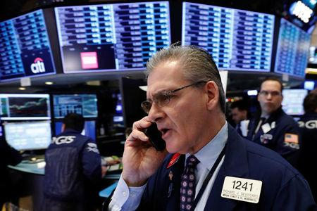 FILE PHOTO: A trader works on the floor of the New York Stock Exchange shortly after the opening bell in New York