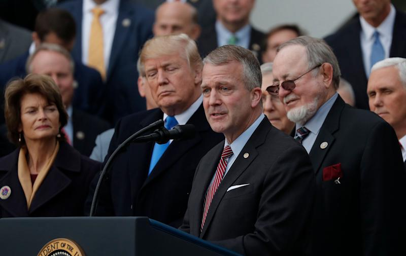 Sen. Sullivan, foreground, speaks at a ceremony celebrating Donald Trump's tax cuts. His fortunes could depend on whether Alaskans distinguish him from the president. (Photo: Carlos Barria/Reuters)