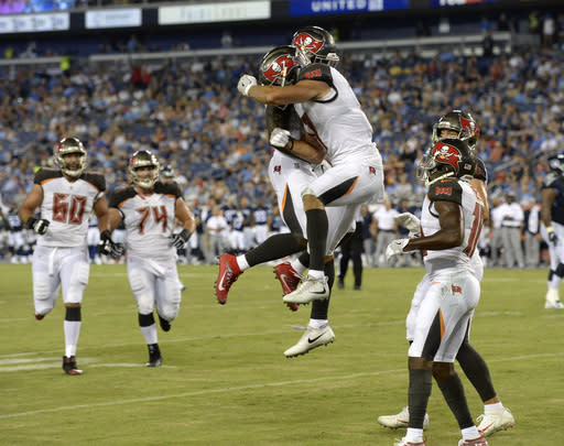 Tampa Bay Buccaneers wide receiver Justin Watson, center right, celebrates with Shaun Wilson, center left, after Watson caught a touchdown pass against the Tennessee Titans in the first half of a preseason NFL football game Saturday, Aug. 18, 2018, in Nashville, Tenn. (AP Photo/Mark Zaleski)