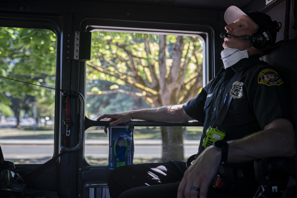 Salem Fire Department paramedic Justin Jones tries to stay cool after responding to a heat exposure call during a heat wave, Saturday, June 26, 2021, in Salem, Ore. (AP Photo/Nathan Howard)