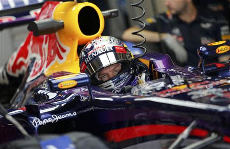 Red Bull Formula One driver Sebastian Vettel of Germany sits in his car during the first practice session of the Abu Dhabi F1 Grand Prix at the Yas Marina circuit on Yas Island, November 1, 2013. REUTERS/