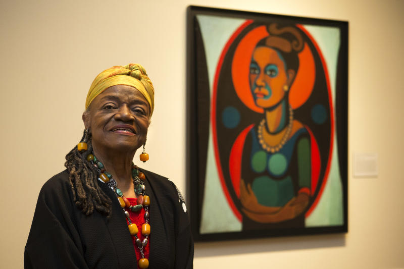 """Artist Faith Ringgold poses for a portrait in front of a painted self-portrait during a press preview of her exhibition, """"American People, Black Light: Faith Ringgold's Paintings of the 1960s"""" at the National Museum of Women in the Arts in Washington on Wednesday, June 19, 2013. Ringgold explains her """"confrontational art"""" _ vivid paintings whose themes of race, gender, class and civil rights were so intense that for years, no one would buy them. """"I didn't want people to be able to look, and look away, because a lot of people do that with art,"""" Ringgold said. """"I want them to look and see. I want to grab their eyes and hold them, because this is America."""" (AP Photo/Jacquelyn Martin)"""