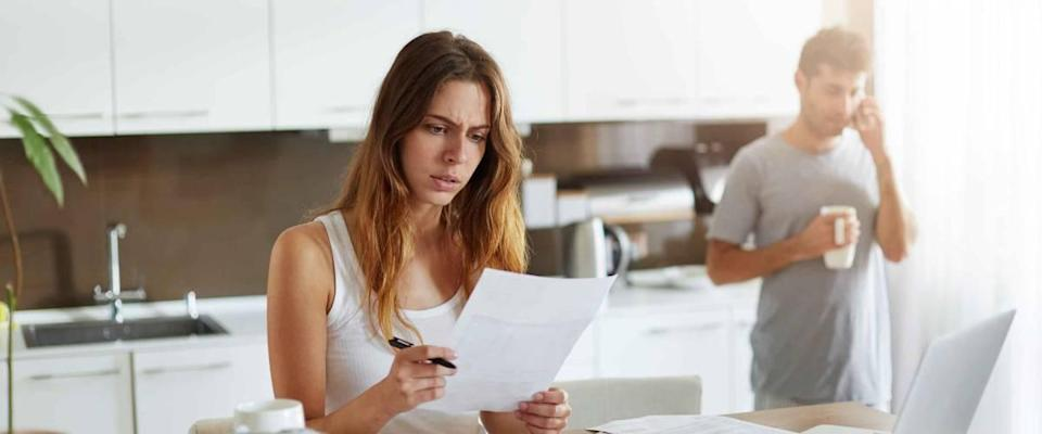 Woman looking at paper sitting at the kitchen table while man in the background on the phone.