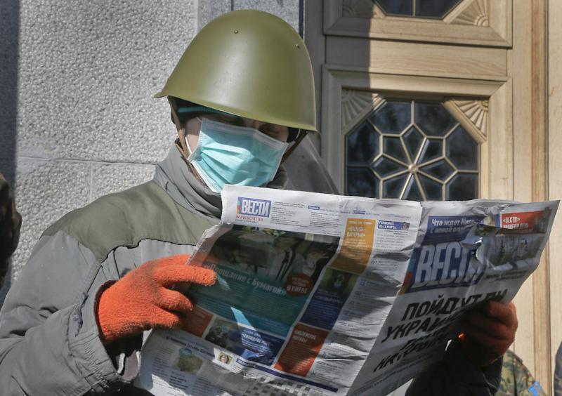 An Ukrainian government supporter reads a news paper as he guards Ukrainian parliament building in Kiev, Ukraine, Tuesday, March 11, 2014. Ukrainian Prime Minister Arseniy Yatsenyuk on Tuesday reiterated his call for Western nations to defend Ukraine against Russia.(AP Photo/Efrem Lukatsky)