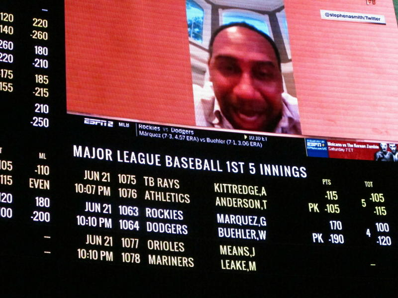 This June 21, 2019 photo shows a video screen listing betting odds at a William Hill sports book inside the Ocean Casino Resort in Atlantic City, N.J. On Monday, June 24, William Hill announced it is donating $50,000 it received from a lawsuit accusing rival FanDuel of copying its betting guide to a New Jersey college to fund creative writing classes. (AP Photo/Wayne Parry)