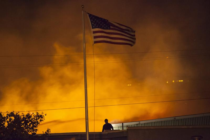 A U.S. flag is seen as a commercial building burns after being ignited by the Sleepy Hollow fire in Wenatchee, Washington