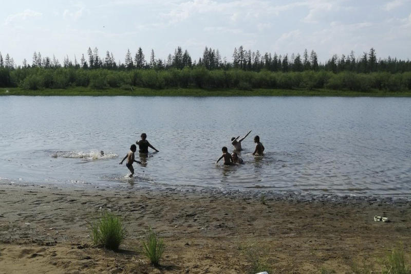 In this handout photo provided by Olga Burtseva, children play in the Krugloe lake outside Verkhoyansk, the Sakha Republic, about 4660 kilometers (2900 miles) northeast of Moscow, Russia, Sunday, June 21, 2020. A Siberian town that endures the world's widest temperature range has recorded a new high amid a hear wave that is contributing to severe forest fires. Russia's meteorological service said the thermometer hit 38 Celsius (100.4 F) on Saturday in Verkhoyansk, in the Sakha Republic about 4660 kilometers (2900 miles) northeast of Moscow. (Olga Burtseva via AP)