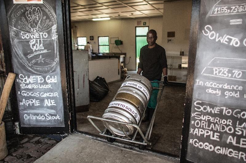 A Soweto Gold craft beer worker pushes beer kegs at the Ubuntu Kraal Brewery on May 13, 2015 in Soweto, Johannesburg (AFP Photo/Gianluigi Guercia)
